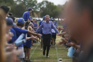 Principal Dale Burden is cheered by students at a sports day
