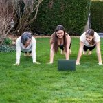 Mother, grandmother and teen daughter practicing fitness lesson online outdoors in garden at quarantine isolation period during coronavirus pandemic. Family doing sport together at home via skype