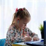Girl schoolgirl in headphones, writes in a notebook.