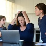 Upset mother forced to work from home as the pandemic coronavirus (COVID-19) forces many employees to work from home.