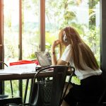 Asian students in uniform with headphone studying in coffee shop using laptop